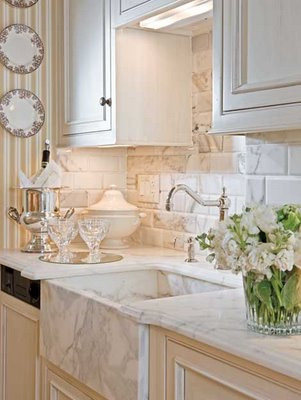 marble countertops, an ultra-deep marble farmhouse sink, and a subway-tile-sized marble backsplash